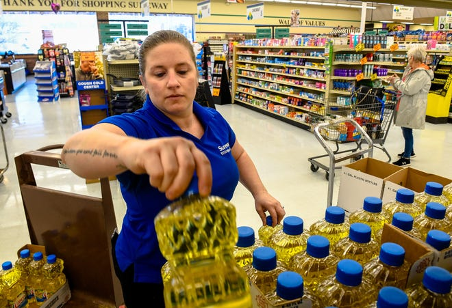 Produce manager Rachel Skelton stocks vegetable oil at the U.S. 41-North Sureway store Wednesday. Grocery stores have had to hire extra workers to keep up with demand during the coronavirus pandemic.