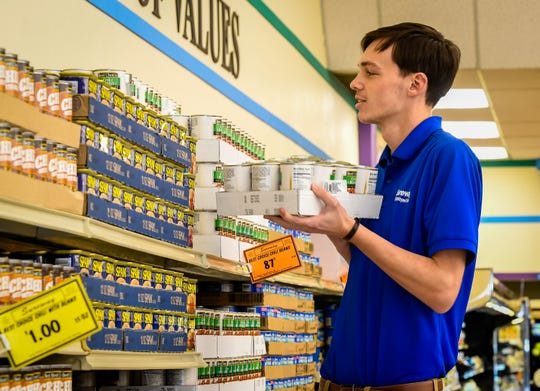 Noah Thomas stocks chili beans Wednesday at the U.S. 41-North Sureway store in Henderson. Grocery stores have been hiring extra people to keep up with demand due to coronavirus.