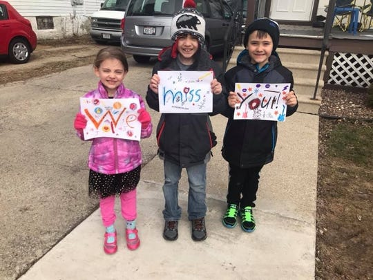 """Children hold signs saying """"we miss you"""" during a Riverside Elementary School parade to visit students during the coronavirus school shutdown."""