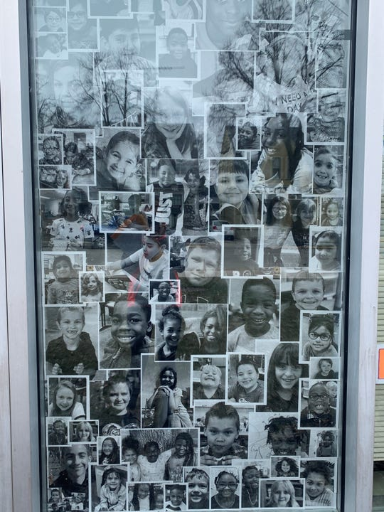 One of Riverside Elementary School's windows has student pictures in its window to let students know they are thinking of them during the coronavirus shutdown .