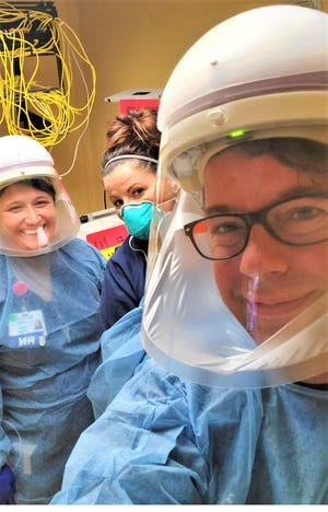 Nursing instructor Ryan Heichel, front, volunteering with others on the COVID-19 unit at Firelands Regional Medical Center.