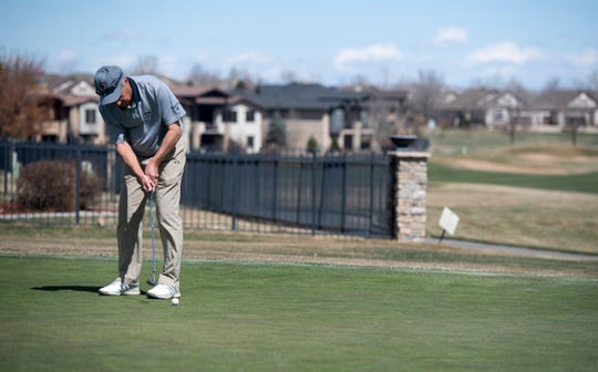 Dave Finnman putts on the putting green with the raised cups in the holes at Highland Meadows Golf Course as businesses respond to the coronavirus pandemic in Windsor, Colo. on Wednesday, March 25, 2020.