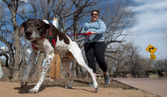 Devyn Richardson walks her dog Finn through Poudre River Whitewater Park during the coronavirus pandemic in Fort Collins, Colo. on Wednesday, March 25, 2020.
