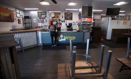 Robert McDougal hands a customer her change for a take out order as the dining room is closed at Jim's Wings in response to the coronavirus in Fort Collins, Colo. on Thursday, March 26, 2020.