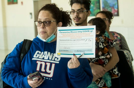 Isamar Miranda displays a certificate she received from a screener at the Southwest Florida International Airport after departing a Frontier Airlines flight from Trenton, New Jersey on Thursday March, 26, 2020. She says there were 10 people on her flight. Screeners from the Department of Health are giving certificates to travelers from the Tri-state area to fill out.
