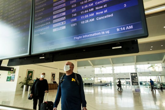 Douglas and Linda Rubinstein from Rhode Island look at the flight information board at Southwest Florida International Airport on Thursday March, 26, 2020.  The couple was heading home early because of the coronavirus pandemic.
