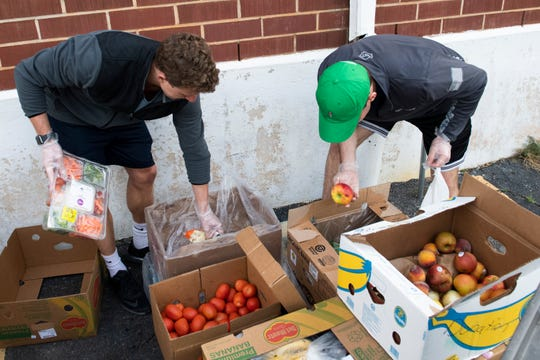 Thomas Berauld (right) and Jon Vandenberg sort through produce to distribute at Harvest Hope Food Bank Thursday, Mar. 26, 2020.