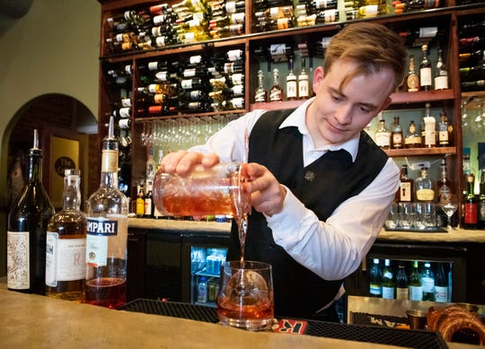 Bartender Elijah Gossett pour a Negroni at SELECT in downtown Greer.