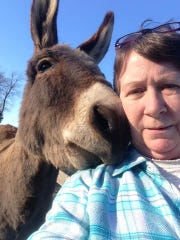 Karen Martin takes a photo with one of her clients, Pete the Donkey.