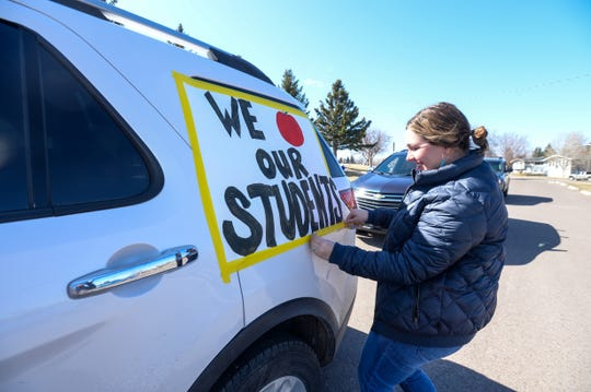 Mountain View Elementary School second grade teacher Brenna Norris tapes a sign to her car ahead of the Mountain View's teacher parade through the various neighborhoods the school serves.