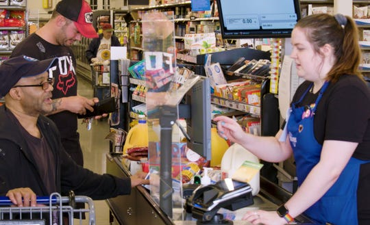 A customer reaches for cash to pay for groceries