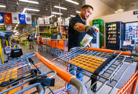Cart hand grips are cleaned and sanitized by Sales Associate Daniel Stone in preparation for use by shoppers at The Home Depot store in Tamuning on Thursday, March 26, 2020. Hardware stores have been designated essential businesses during the pandemic.
