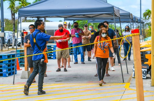 Sales Associate Travis Torres allows a customer to enter as other shoppers remain in line, spaced six feet apart, outside at The Home Depot store in Tamuning on Thursday, March 26, 2020. Due to the coronavirus, or COVID-19, pandemic, a single entrance and single exit was implemented at the store, in efforts to limit the number of shoppers to only 130 customers at a time, said Store Manager Raymond Gomez. Gomez added that future shipments of masks and gloves, will be donated to the hospital and first responders as they help treat those affected by the pandemic.