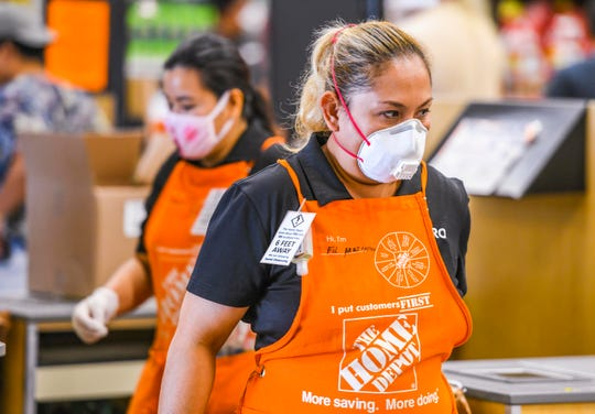 A small placard, worn by Fileminia Cruz and other Home Depot employees, serve as a friendly reminder to customers of social distancing on Thursday, March 26, 2020. In light of the pandemic of the coronavirus, measures have been implemented at the hardware outlet in order to help stem the spread of the virus, said Raymond Gomez, store manager.