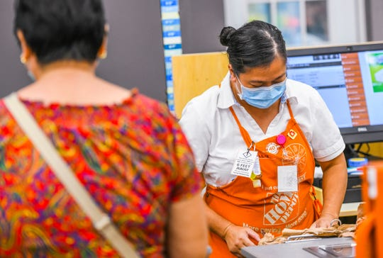 A small placard, worn by cashier Nellie Santelices and other Home Depot employees, serve as a friendly reminder to customers of maintaining social distancing on Thursday, March 26, 2020.