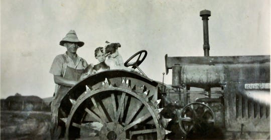 """Margaret Probasco of rural Swisher thinks she was only about three years old in this 1930 photo of her father, Milo Novak, and her dog Pinker on the family's steel-wheeled farm tractor. """"I think it was a Farmall,"""" she added. """"My dad always had Farmalls."""" As renters, the family moved from farm to farm several times during the Great Depression"""