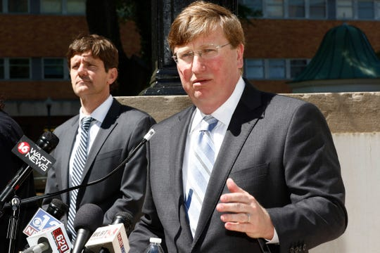 Gov. Tate Reeves speaks to reporters clarifying his earlier issued executive order regarding COVID-19 issues, during a news conference outside the Governor's Mansion, Thursday, March 26, 2020 in Jackson, Miss. (AP Photo/Rogelio V. Solis)