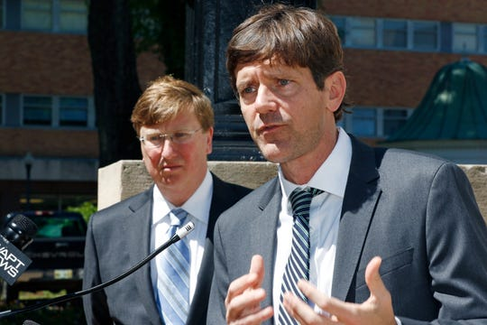 State Health Officer Dr. Thomas Dobbs, speaks about establishment of two one-day COVID-19 testing centers in Clarksdale and Olive Branch Friday, during a news conference outside the Governor's Mansion, while Gov. Tate Reeves, left, listens, Thursday, March 26, 2020 in Jackson, Miss. The testing centers will be run by the Mississippi State Department of Health and the University of Mississippi Medical Center. (AP Photo/Rogelio V. Solis)