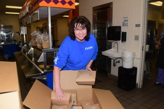 Volunteer Donna Watson organizes boxes of sandwiches and chips at the Knox County School food distribution program held at Karns Middle School Wednesday, March 25.