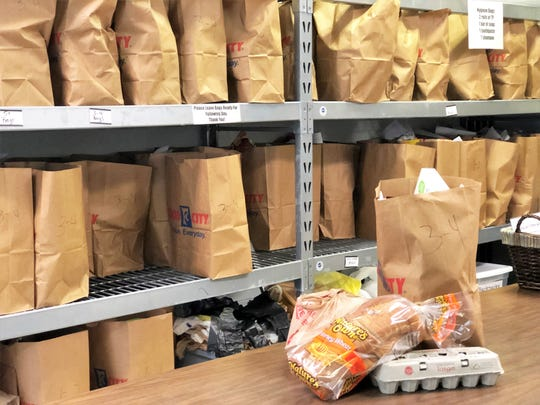 """Inside the Fountain City Ministry, grocery bags have already been filled to hand out the next day and include canned goods, toilet paper, eggs and bread. """"Yesterday two high school boys delivered bags to people who could not drive themselves to the center,"""" said operations manager Kelly Gregory. March 25, 2020."""