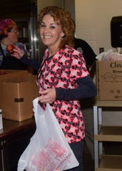 Cindy Cline is all smiles packaging fruit and carrots at the Knox County School food distribution program held at Karns Middle School Wednesday, March 25.