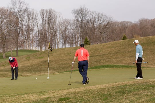Keith Spalding, left, putts as Dave Delk, center, and Joe Dexter, right, watch on at Purdue's Ackerman-Allen Golf Course, Thursday, March 26, 2020 in West Lafayette.
