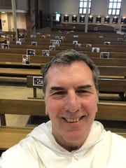 Fr. Patrick Baikauskas did his best this week to remember where parishioners typically sat at St. Thomas Aquinas' sanctuary after asking the West Lafayette congregation to send him selfies and family portraits to fill the church's empty pews during the days of social distancing to help curb the spread of coronavirus.