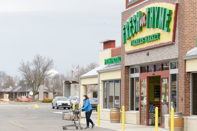 Shoppers walk out of Fresh Thyme Farmers Market, Thursday, March 26, 2020 in West Lafayette.