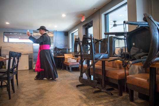 Chairs and tables stacked against a wall as Reverend Monsignor Christopher Nalty, pastor of Good Shepherd Parish in New Orleans, blesses Station 6 seafood and oyster bar in Bucktown on Friday, March 20, 2020.