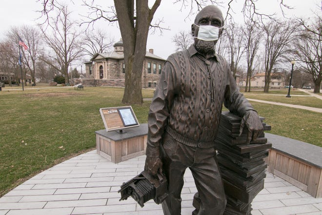 """Howell Carnegie District Library is among several libraries and city and village offices closing buildings to the public. Someone placed a mask on the """"Zemp Legacy"""" statue in front of the library, shown Thursday, March 26, 2020."""