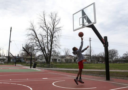 """Sad"" is what Justin Green felt as he shot towards a rimless hoop while playing on the basketball courts at the Wyandotte Park Thursday afternoon. Metro Parks took down the rims at many parks to discourage crowds due to the coronavirus outbreak. The 10-year-old shot at the goal for around 20 minutes before giving up. His basketball league was cancelled due to the outbreak as well."