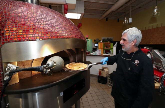 Anoosh Shariat, owner/chef of Noosh Nosh, removed a hot pizza from the oven for a takeout order to be delivered curbside in Louisville, Ky. on Mar. 25, 2020.  Noosh Nosh has been providing the service to its customers following the governor's order to close in-service dining at restaurants and bars due to concerns over the coronavirus outbreak.