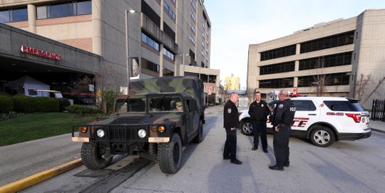 A Kentucky National Guardsman and LMPD officers chatted outside the Univeristy of Louisville Hospital in Louisville, Ky. on Mar. 26, 2020.  They have started maintaining shifts at the hospitals at the request of the governor to keep a presence there due to concerns over the coronavirus outbreak.