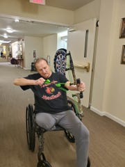 Donnie Emert takes aim with a Nerf bow and arrow set at Windsor Ridge assisted living home in Jeffersonville, Indiana.