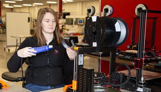 Graduate assistant and student Kate Schneidau oversees the 3D printing of face shield for local health care professionals in response to the shortage caused by the COVID-19 pandemic. University of Louisville