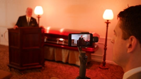 Funeral director Sean Snyder, right, of Snyder Funeral Homes perfects the firm's program of live-streaming funeral ceremonies. He and other directors at the firm make live-streaming of funeral services available from every location of Snyder Funeral Home, an option that has proven popular with families especially during the ongoing coronavirus pandemic.