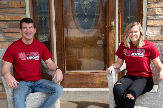 """Rick Petfalski and Muskego High School student Faith Kierzek wear """"Muskego Strong"""" T-shirts. They are being sold to help local businesses and community members in need due to the coronavirus pandemic."""