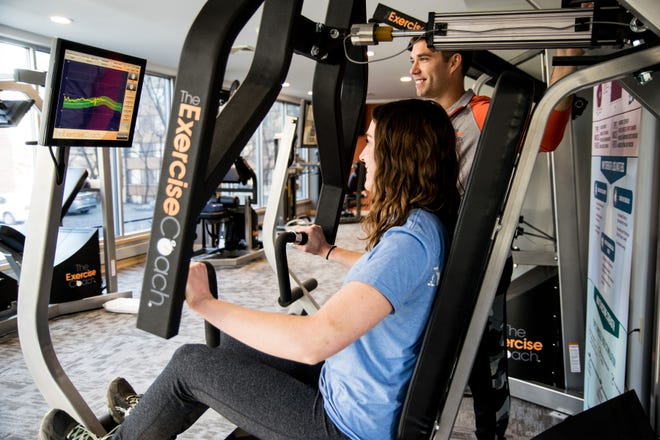Dylan Dreger, owner of The Exercise Coach in Shorewood, guides Melanie Branecky through a bench press workout.