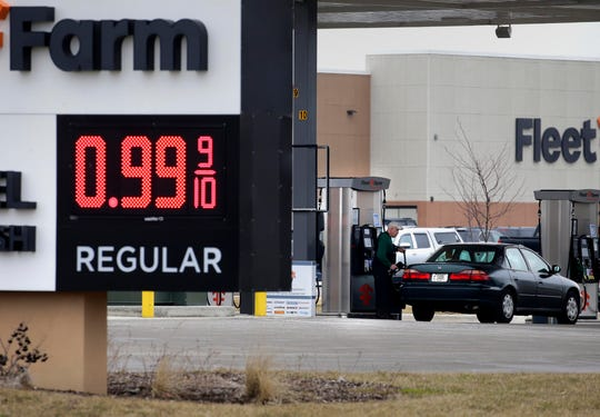 A customer pumps gas into his tank at Fleet Farm in Delavan, Wisconsin, near I-43  and Highway 50, which is selling gasoline for .99 per gallon as gas prices drop during the coronavirus pandemic, Thursday March 26, 2020.