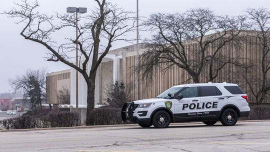 A Greendale police officer looks over the empty Southridge mall parking lot on Wednesday, March 25, 2020, the first day of Gov. Tony Evers' safer-at-home order. The action was put into place to stop the spread of the coronavirus.