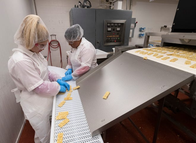 Workers produce jalapeño cheese snack products Thursday, March 26, 2020 at the Specialty Cheese Co. Inc. in Reeseville, Wis. The Dodge County cheese maker has been swamped with orders for shelf stable cheese snacks, such as these Just The Cheese, crunchy toasted cheese snacks.