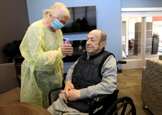 Johanna Mannone, 79 of Rochester Hills gets her son Michael Mannone, 49, to talk to his father Michael Mannone, 71 on her iPhone during his visit with his wife at WellBridge of Rochester Hills, a skilled nursing and rehabilitation center in Rochester Hills, Michigan.