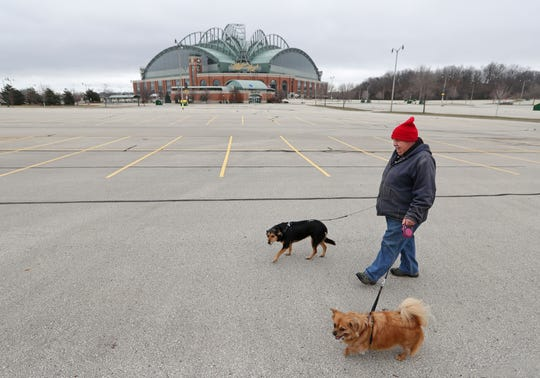 Tom Giesfeldt of Milwaukee walks his dogs in an empty Miller Park parking lot on what would have been the Milwaukee Brewers' opening day game against the Chicago Cubs in Milwaukee on Thursday, March 26, 2020. The game was postponed due to the coronavirus pandemic.