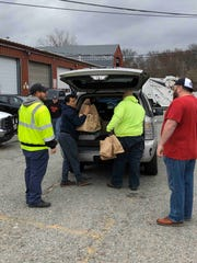 "Volunteers on a ""Feeding the Front Line"" drive in Morris County deliver meals to first responders: volunteers bring a delivery from Parsippany's Best Pizza to the township DPW."
