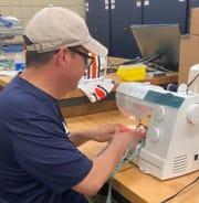 Auburn associate athletics director for equipment operations, Dana Marquez, sews surgical Masks.