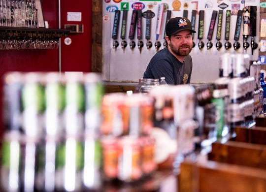 David Bradley, of the Autauga Creek Craft House in Prattville, Ala., works selling craft beer to go instead of selling them in-house at the bar on Thursday March 26, 2020.