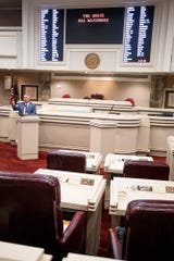 Alabama Speaker of the House Mac McCutcheon talks to the media after a quorum call in the nearly empty house chamber at the Alabama Statehouse in Montgomery, Ala., on Thursday March 26, 2020.