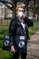 Jared Park poses for a portrait wearing a mask and with his DJ deck at the East Park Thursday, March 26, 2020, in Nashville, Tenn. Park is no longer able to DJ due the coronavirus and subsequent bar closures.