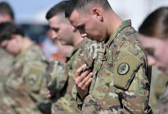 Tennessee National Guard members pray Thursday, March 26, 2020, in Smyrna, Tenn., before they are sent to assist in the fight against the coronavirus in counties through the state.