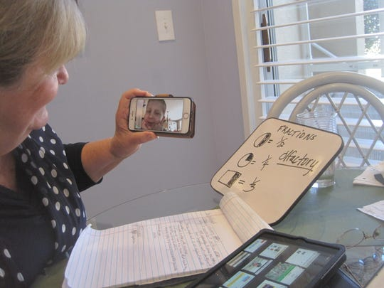 Velma Theisen waits for a reply from her grandson during a lesson on fractions.